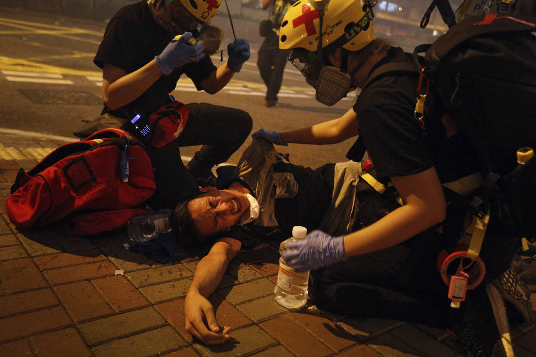 Medical workers help a protester in pain from tear gas fired by policemen on a street in Hong K ...