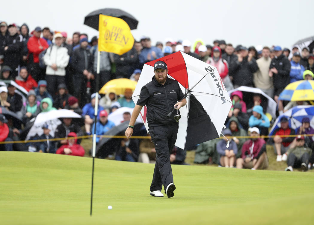 Ireland's Shane Lowry walks with his umbrella on the 6th green during the final round of the Br ...