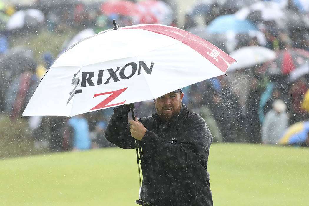 Ireland's Shane Lowry holds an umbrella in heaven rain on the 8th green during the final round ...