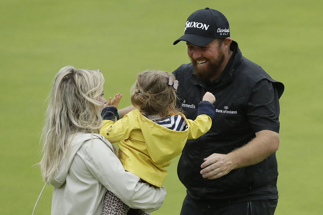 Ireland's Shane Lowry goes to kiss his daughter Iris and hugs his wife Wendy Honner on the 18th ...