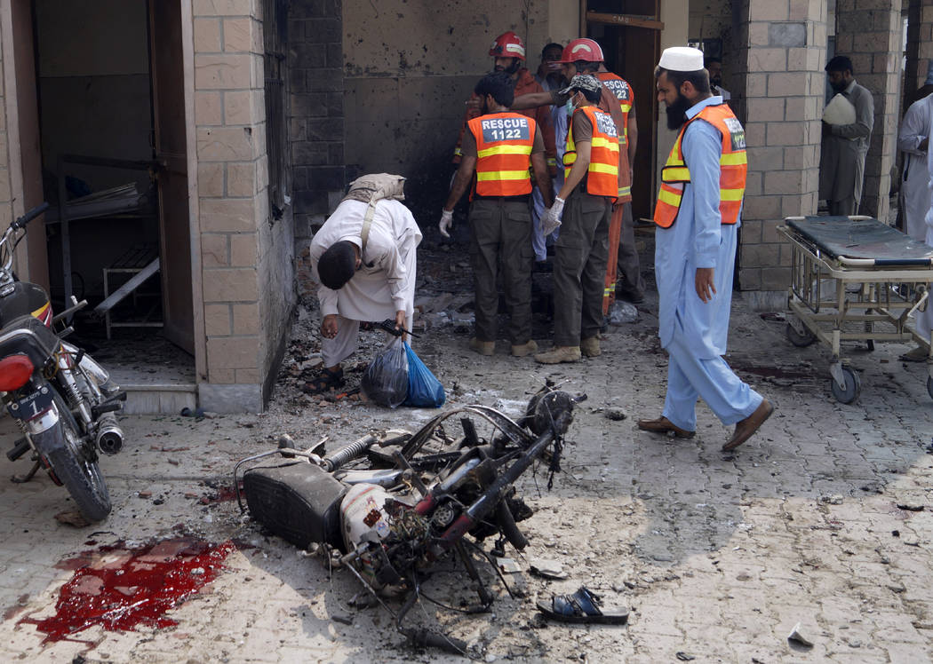 Pakistani security officials and rescue workers gather at the site of a bombing on an entrance ...