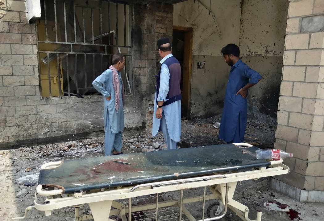 Hospital staff gather at the site of a bombing on an entrance of a hospital in Dera Ismail Khan ...