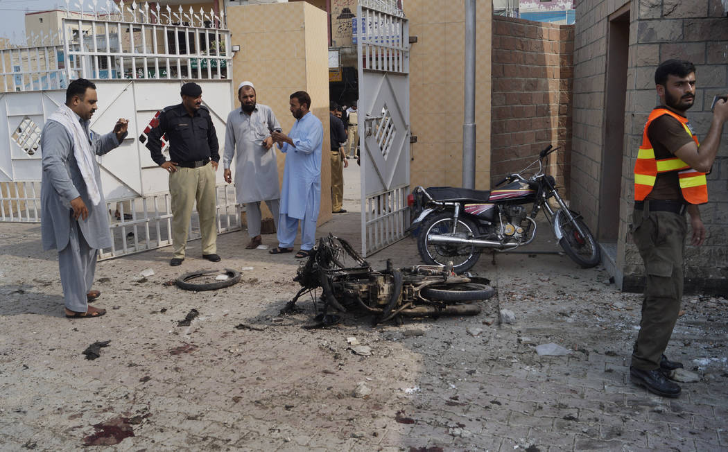 Pakistani security officials examine the site of a bombing on an entrance of a hospital in Dera ...