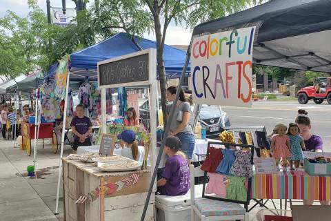 Budding entrepreneurs set up booths on the sidewalk, to sell their products during the Children ...