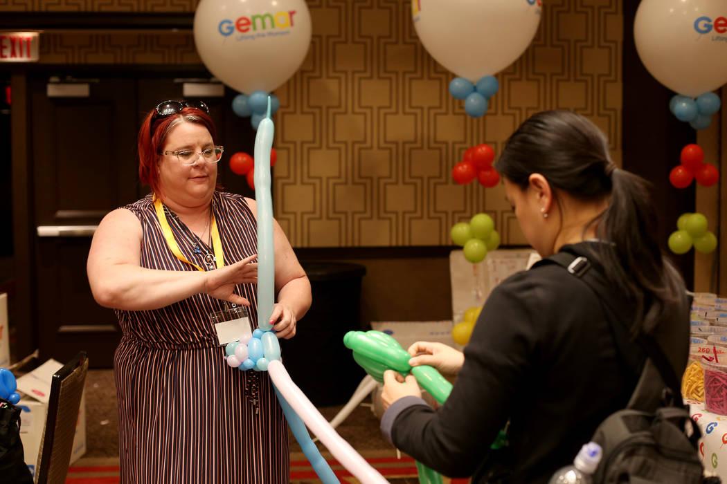 Becky Killoran of Canada, left, and Angie Tsang, of California, right, play with balloon twisti ...