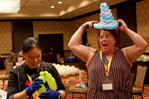 Angie Tsang, of California, left, and Becky Killoran of Canada, right, play with balloon twisti ...