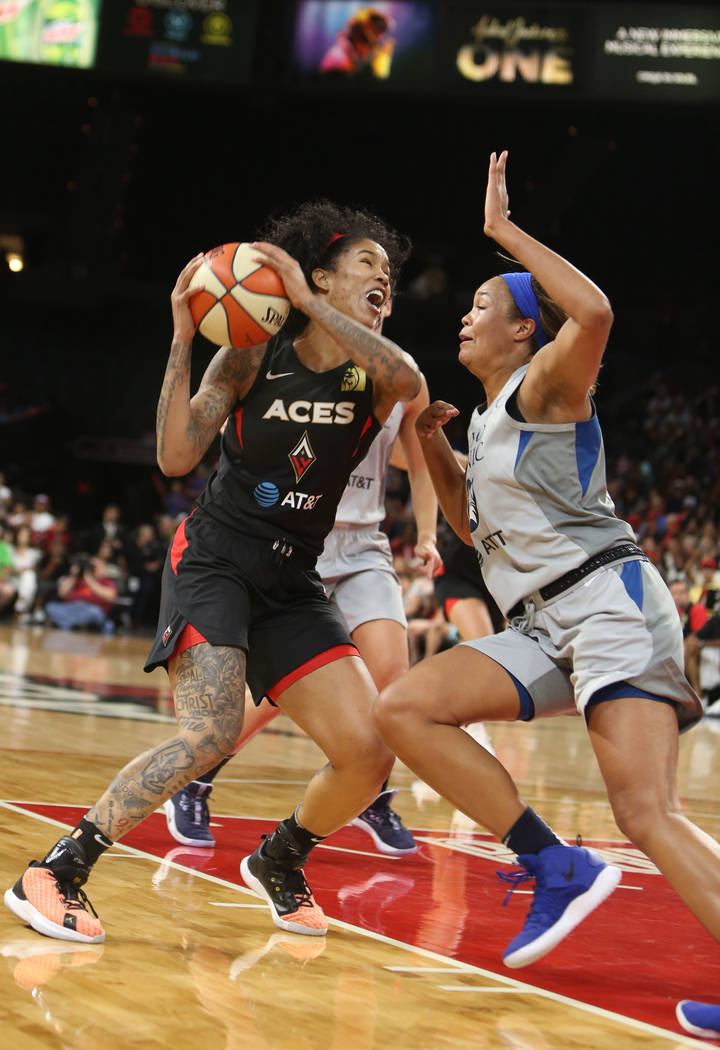 Las Vegas Aces forward Tamera Young, left, fights to the hoop against Minnesota Lynx forward Na ...