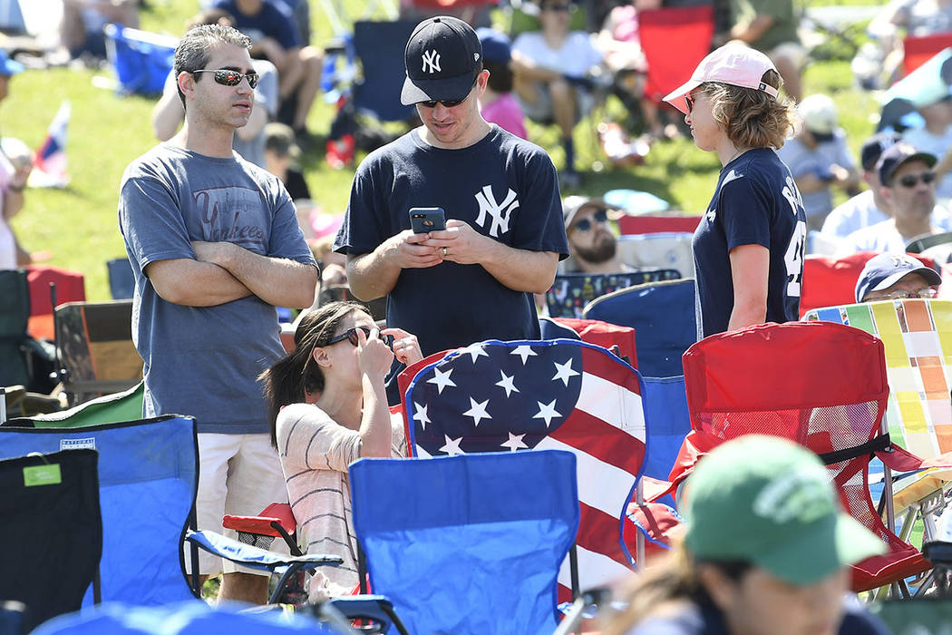 Fans wait for the start of the National Baseball Hall of Fame induction ceremony at the Clark S ...