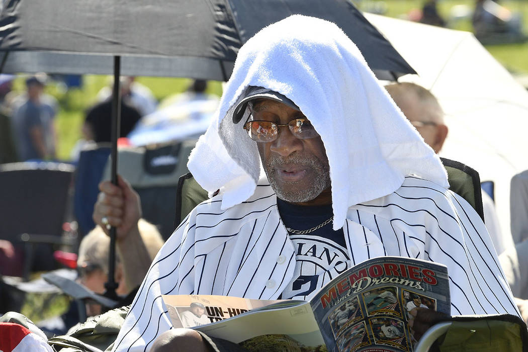 Mariano Rivera fan Eugenino Edwards, of New York uses a towel to keep cool before the National ...