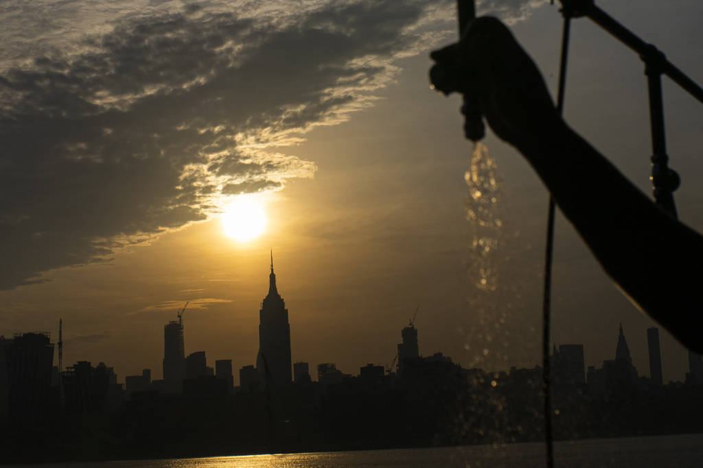 The sun rises over New York City and the Empire State Building while a man sprays water at Pier ...