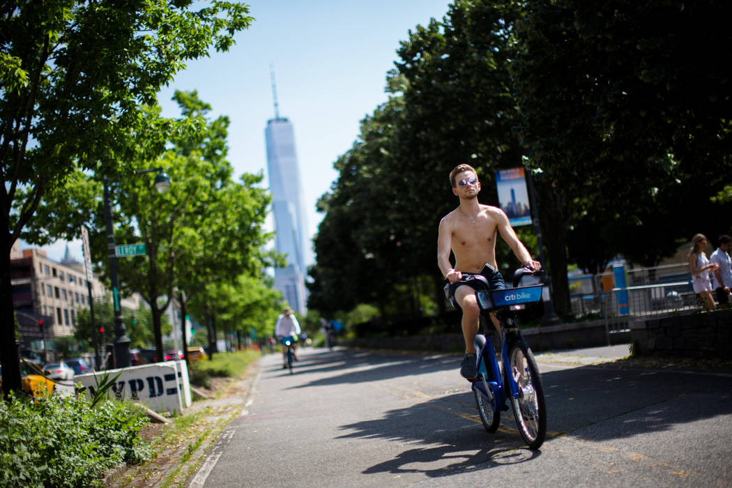 Cyclists ride down a path near the Hudson River during high temperatures on Saturday, July 20, ...
