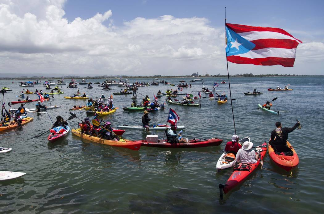 Demonstrators in kayaks gathered in front of La Fortaleza for an aquatic protest against Puerto ...