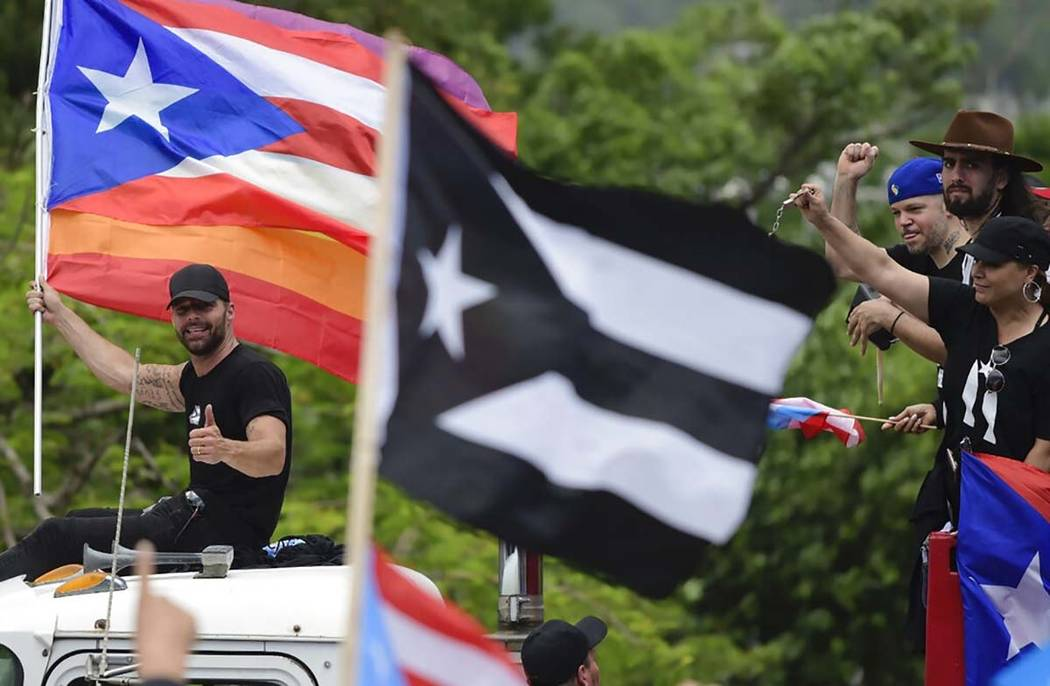 Ricky Martin, holding a Puerto Rican flag and a rainbow banner, flashes a thumbs up as he joins ...