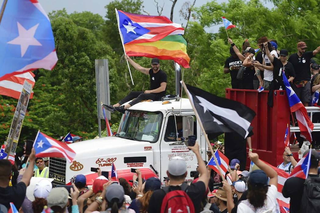 Ricky Martin, holding a Puerto Rican flag and a rainbow banner, joins thousands of Puerto Rican ...