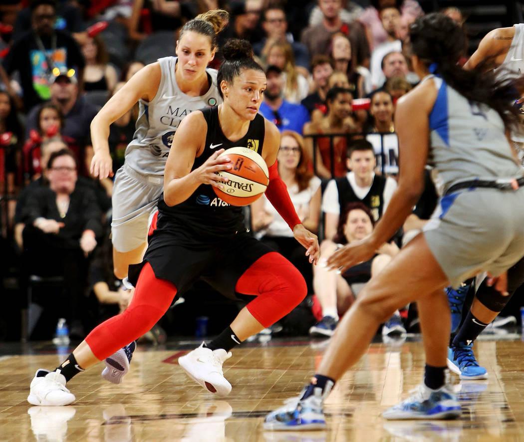 Las Vegas Aces point guard Kayla McBride (21) dribbles the ball against Minnesota Lynx guard Le ...