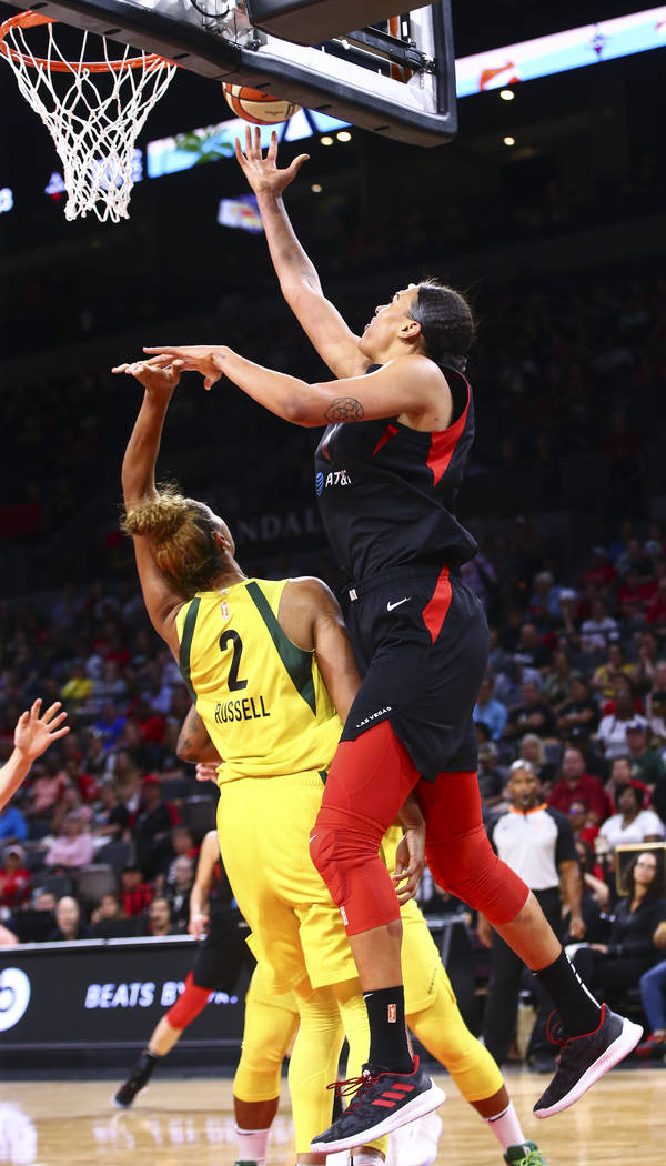 Las Vegas Aces' Liz Cambage, right, lays the ball up past Seattle Storm's Mercedes Russell (2) ...