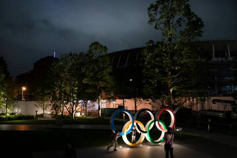 Two children pose for photos with the Olympic Rings in front of New National Stadium in Tokyo, ...