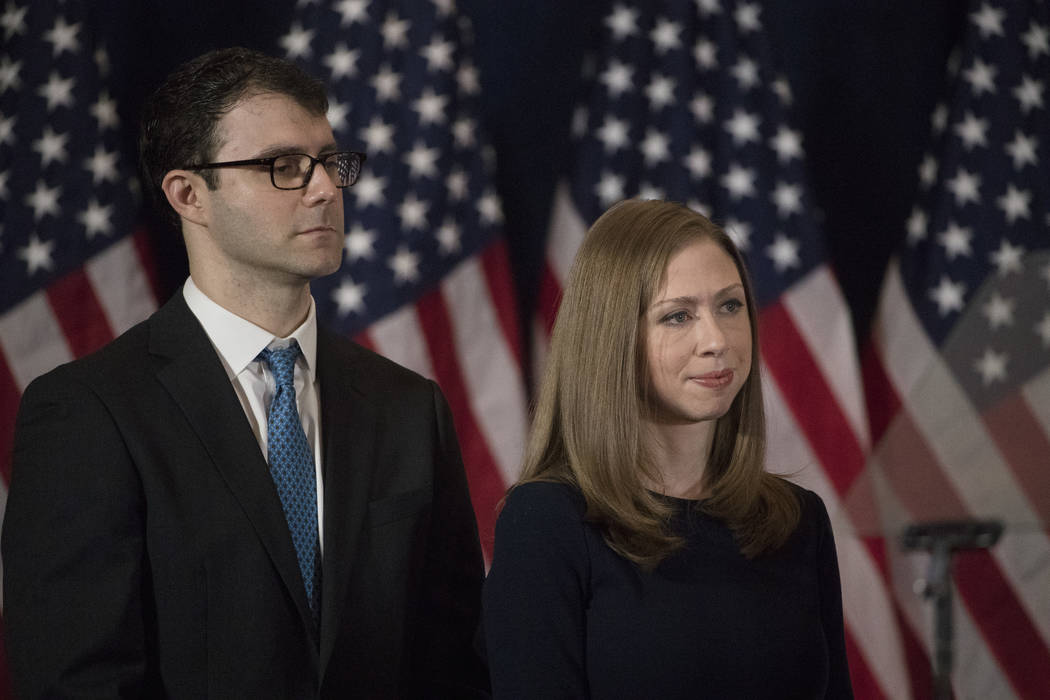FILE - In this Nov. 9, 2016 file photo Chelsea Clinton and her husband Marc Mezvinsky listen to ...