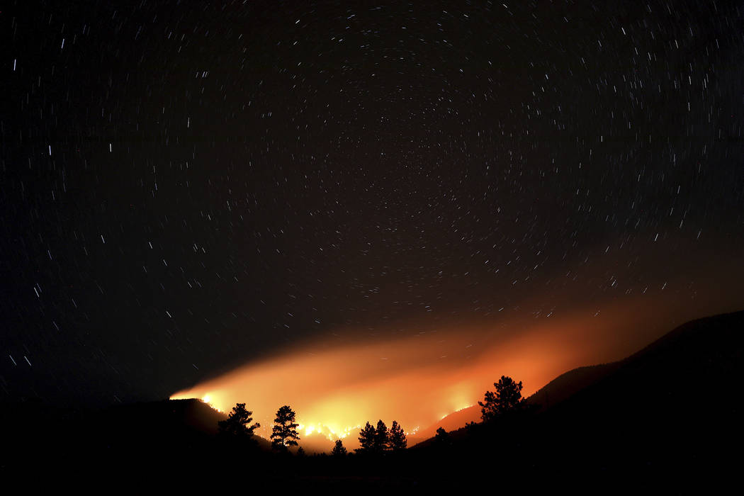 Pockets wildfires within the Museum fire create an ocean of light lapping at the slopes of the ...