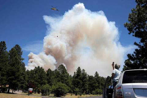 A helicopter carries a bucket of water to attack hot spots on the Museum Fire in Flagstaff, Ari ...