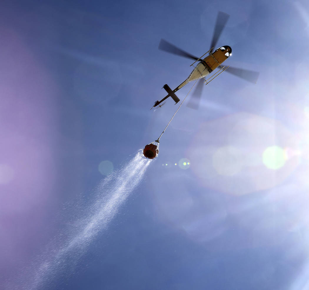 A helicopter drags a Bambi Bucket full of water through the sky on it's way to quench hot spots ...