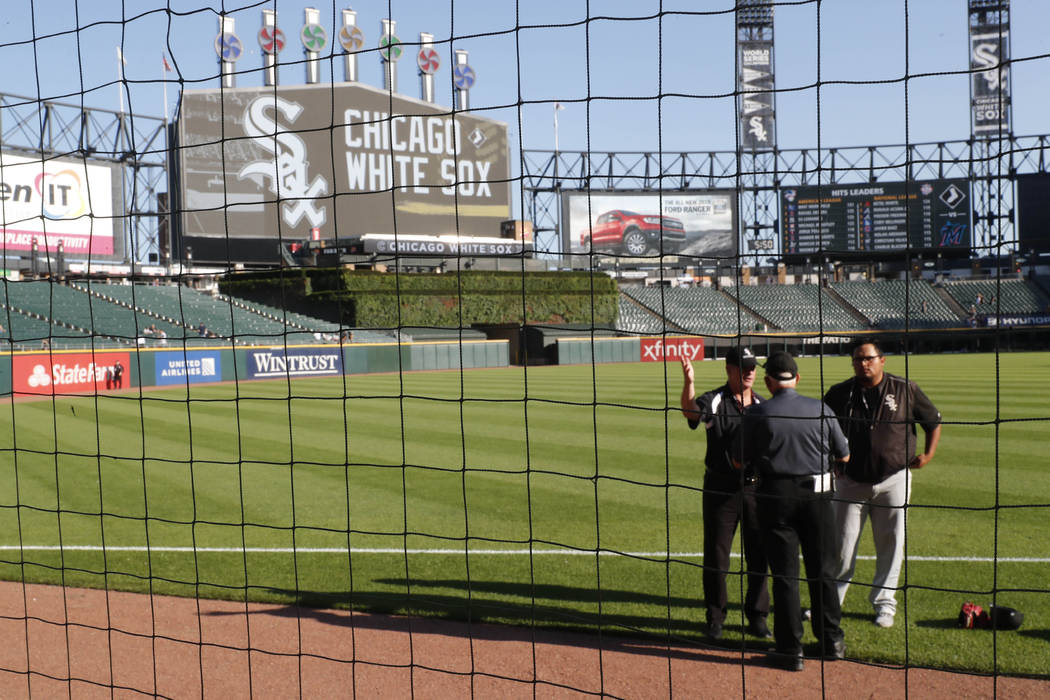 Security personnel at Guaranteed Rate Field are viewed through the newly extended protective ne ...