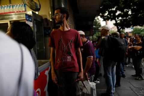 People walk in the streets of Caracas after a massive blackout left the city and other parts of ...