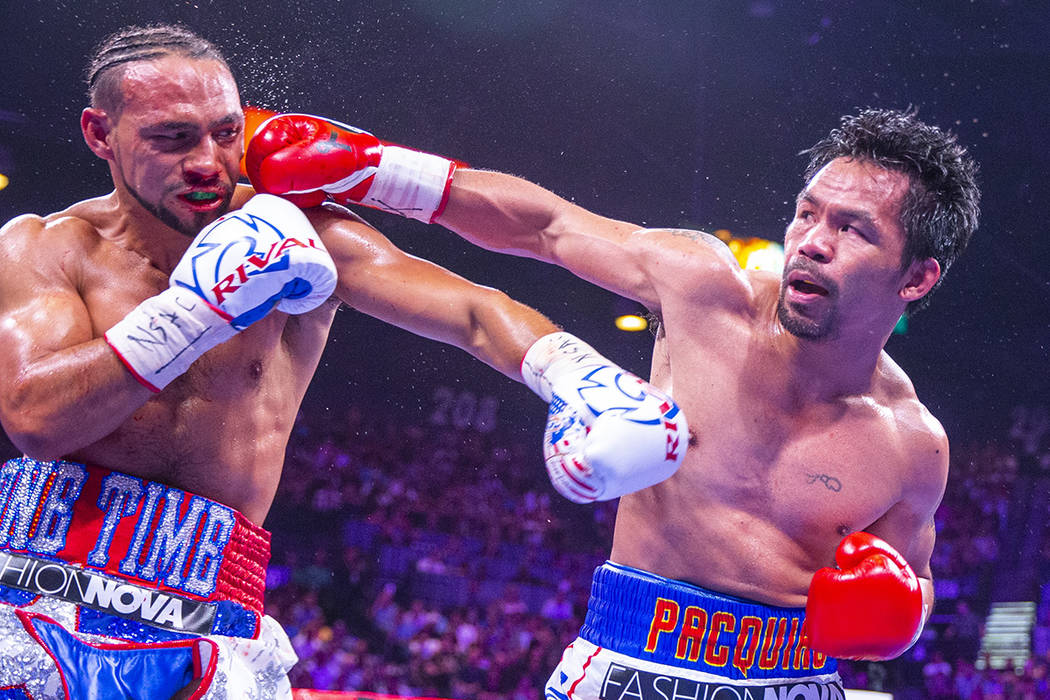Keith Thurman is punches in the face by Manny Pacquiao during Round 5 of their WBA super welter ...