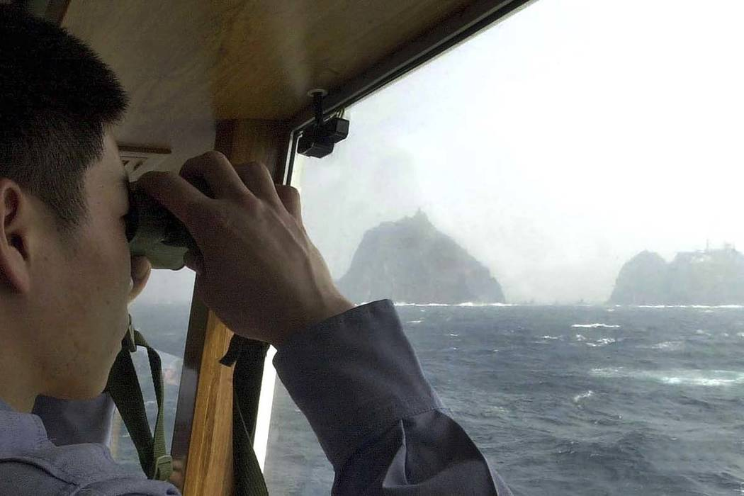 In this April 28, 2005, file photo, a South Korean coast guard looks at Dokdo islets, known as ...