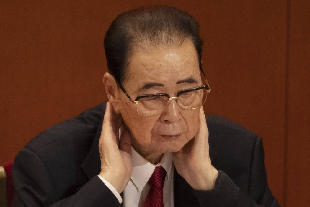 In a Oct. 24, 2017, photo, former Chinese Premier Li Peng, places his hands around his neck dur ...