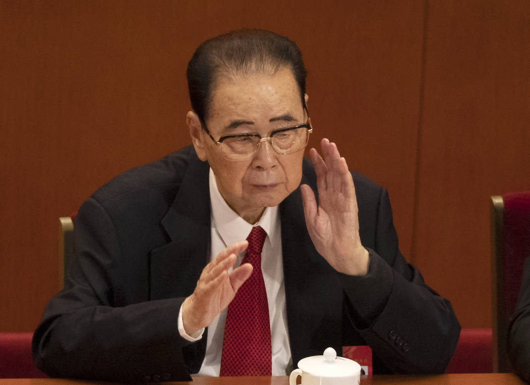 In this Oct. 24, 2017, photo, former Chinese Premier Li Peng, reach for his neck during the clo ...