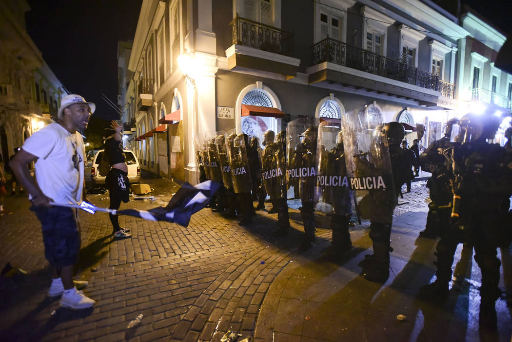 Demonstrators stand in front of riot control units during clashes in San Juan, Puerto Rico, Mon ...