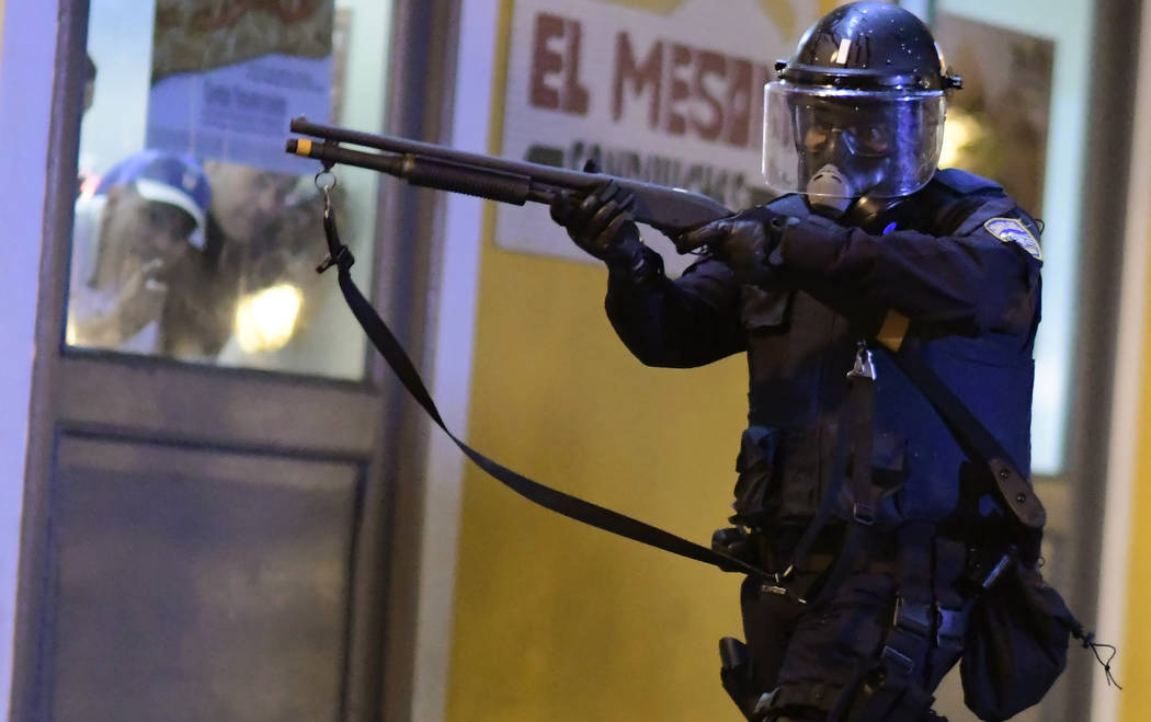 A member of the riot control units patrol the street while people look out the window during cl ...