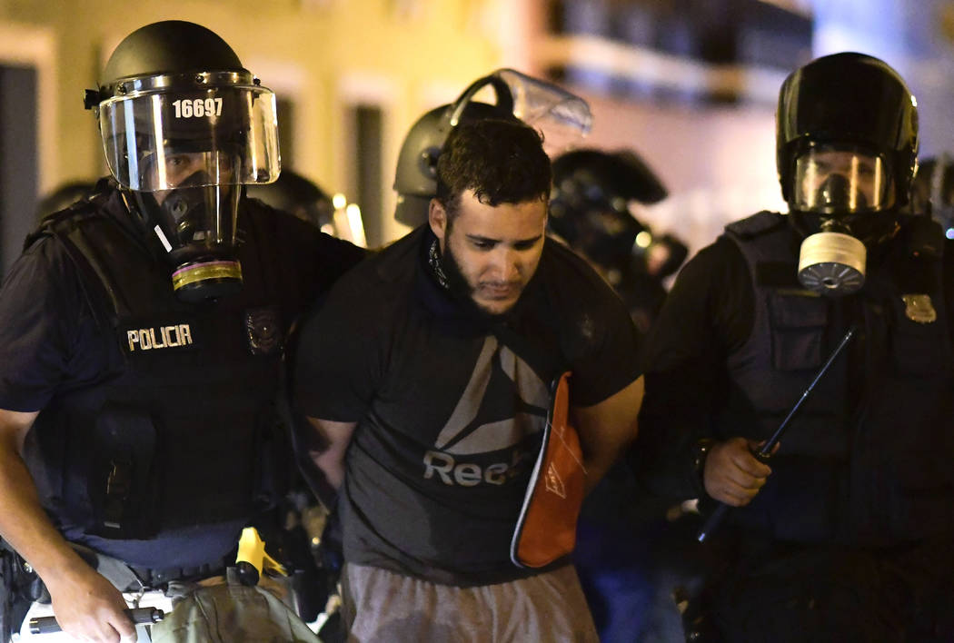 Police arrest a demonstrator during clashes demand the resignation of Gov. Ricardo Rossello in ...