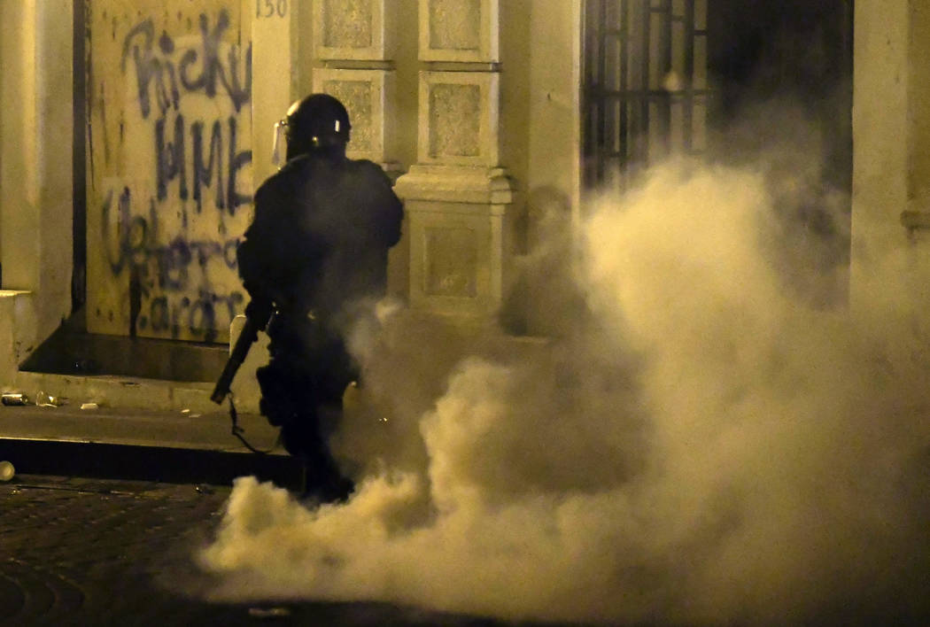 A member of the riot control units patrol the street during clashes in San Juan, Puerto Rico, M ...
