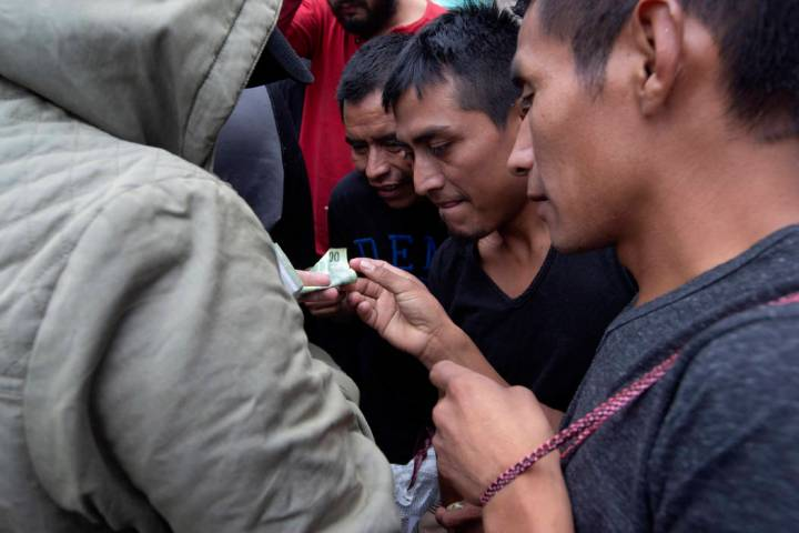 Guatemalan men who were deported from the United States, change money after arriving at the Air ...