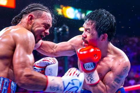 Keith Thurman, left, is punched in the face by Manny Pacquiao during Round 12 of their WBA supe ...