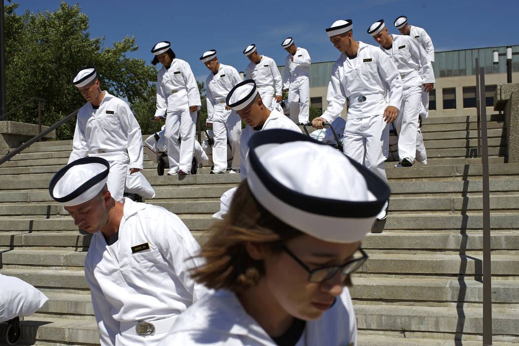 FILE - In this June 27, 2019, file photo, incoming plebes carry their belongings down a stairca ...