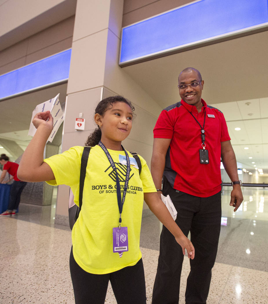 Malia English, 8, practices paper plane throwing with volunteer Frederick Kuforiji during the s ...