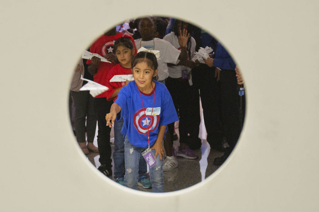Maria Garcia, 8, attempts to land a paper plane through a hole during the seventh annual Paper ...