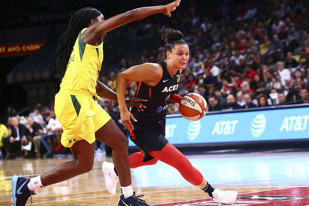 Las Vegas Aces' Kayla McBride, right, drives to the basket past Seattle Storm's Crystal Langhor ...