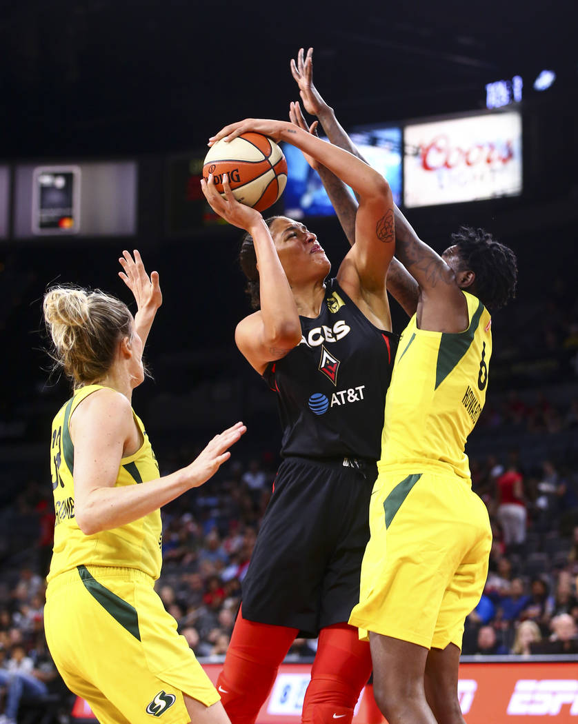Las Vegas Aces' Liz Cambage, center, goes to the basket between Seattle Storm's Sami Whitcomb, ...