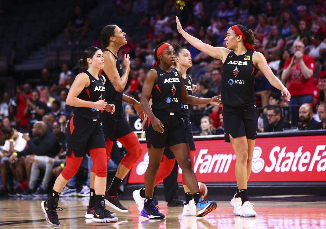 Las Vegas Aces players react during a break in the first half of a WNBA basketball game against ...