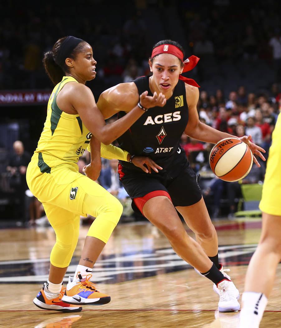 Las Vegas Aces' Dearica Hamby (5) drives to the basket past Seattle Storm's Jordin Canada durin ...