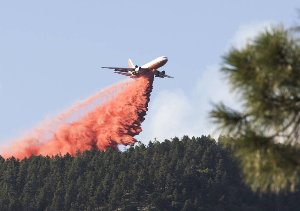 In this Sunday, July 21, 2019, photo, a tanker releases a wave of fire retardant into the crest ...