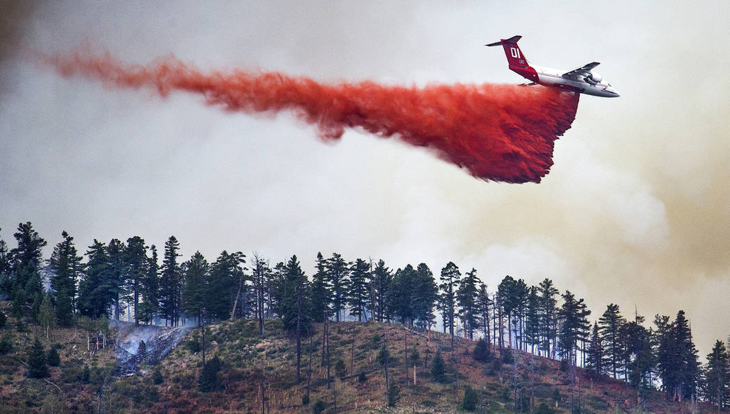 In this Monday, July 22, 2019, photo, an air tanker drops retardant on a ridge overlooking the ...