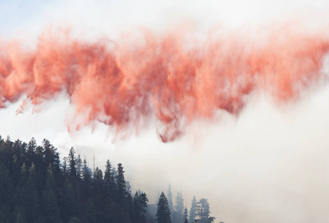 In this Sunday, July 21, 2019, photo, a wave of fire retardant prepares to touch down on the ed ...