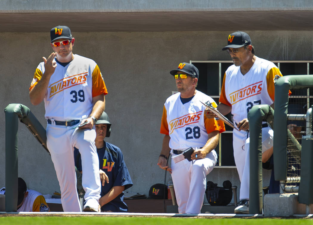 Aviators manager Fran Riordan (39) sends in signals to his batter with coaches Craig Conklin (2 ...