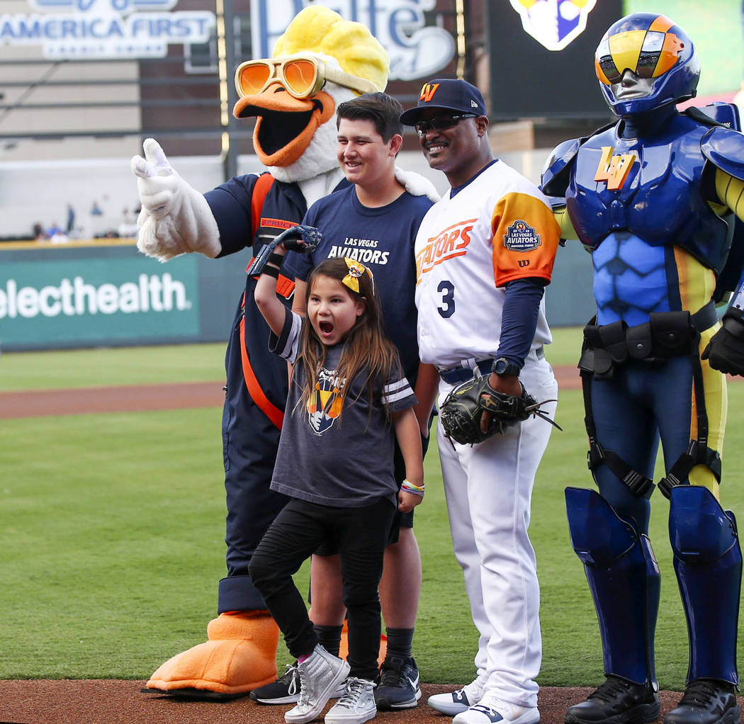 Nine-year-old Hailey Dawson, center, poses after throwing the first pitch with, from left, Spru ...