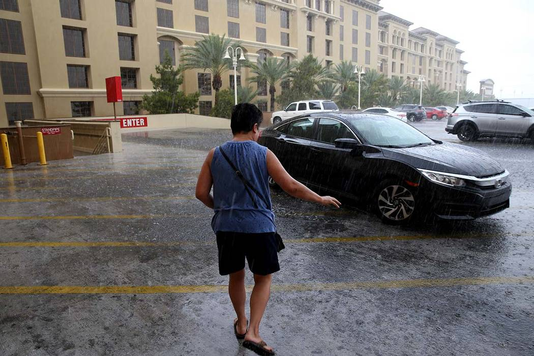 Keith Carbullido pulls up the car for his wife, Rosa Carbullido, in a downpour at Green Valley ...